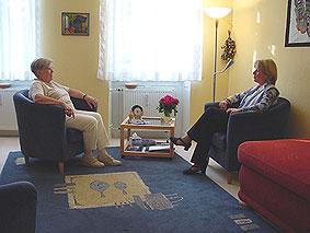 In einem freundlichen Raum sitzen sich zwei Menschen in einem Beratungsgespräch gegenüber